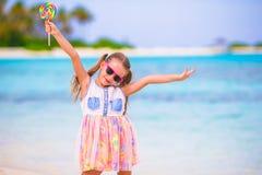 可爱的小女孩获得与棒棒糖的乐趣在 免版税库存图片