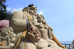 """""""秀丽和野兽""""铺沙雕塑 库存照片"""