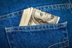 堆在牛仔裤的一百元钞票装在口袋里 免版税库存照片
