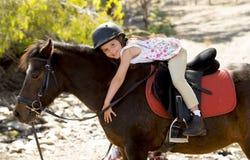 拥抱小马马微笑的愉快的佩带的安全骑师盔甲的甜女孩在暑假 免版税库存图片