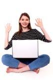 有个人计算机胳膊的逗人喜爱的妇女提高了好消息股票图象 免版税库存照片