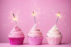 与闪烁发光物的桃红色杯形蛋糕 免版税库存照片
