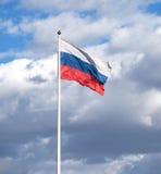 在挥动在多云天空的旗杆的俄国旗子 免版税库存照片