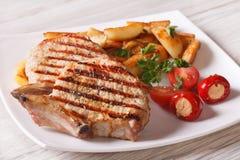 烤猪肉牛排用土豆和菜在板材 免版税库存照片
