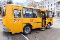 Το δημόσιο σχολικό λεωφορείο που σταθμεύουν επάνω στην οδό περιμένει να συλλέξει το σχολείο Στοκ Εικόνες