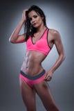 摆在性感的健身穿戴的肉欲的妇女 免版税图库摄影