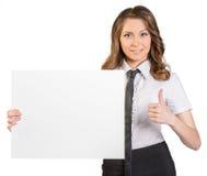拿着白色空白的海报的年轻女商人 库存图片