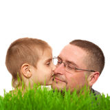 父母孩子亲吻父亲节绿草白色 免版税库存图片