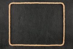绳索,在黑自然皮革的背景的谎言框架  免版税库存照片