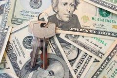 在金钱背景的钥匙  买或租赁家的概念 图库摄影