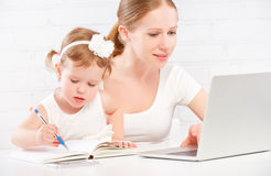 愉快的家庭母亲和在家研究计算机的儿童婴孩 免版税库存图片