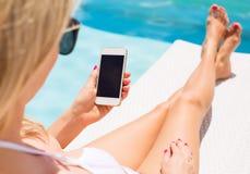 晒日光浴在椅子由水池和使用手机的妇女 免版税库存图片