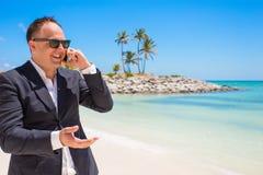 商人谈话在电话在海滩 免版税库存照片