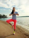 Γυναίκα ικανότητας που κάνει τις ασκήσεις γιόγκας στην παραλία άμμου του ποταμού Στοκ εικόνα με δικαίωμα ελεύθερης χρήσης