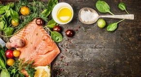 有盐、新鲜的草本和香料匙子的未加工的三文鱼鱼片在土气木背景,顶视图,横幅 免版税图库摄影