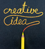 黄色铅笔在黑工艺纸写创造性的想法词 库存图片