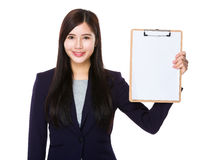 与剪贴板空白页的年轻女实业家展示  免版税库存图片
