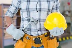 拿着锤子和安全帽的杂物工的综合图象 库存照片