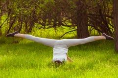 做在绿草的女孩瑜伽 图库摄影