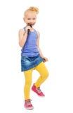 唱歌在话筒和跳舞的愉快的女孩 免版税库存照片