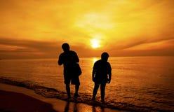 父亲和儿子剪影在海滩散步 库存图片