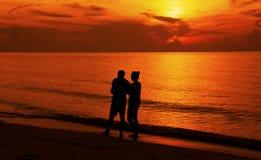 走在海滩的夫妇的剪影在日落 免版税库存图片