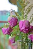 枯萎与权利的桃红色和绿色花玫瑰多数花在一个花瓶的焦点在阳台 免版税库存图片