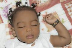 睡觉在她的屋子(一岁)里的可爱的女婴 库存照片