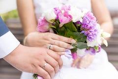 拿着美丽的新娘花束的新娘和新郎特写镜头  库存照片
