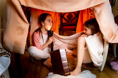 姐妹讲可怕故事在毯子下在晚上 免版税图库摄影