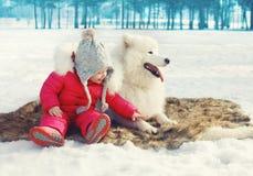 有白色萨莫耶特人狗的愉快的孩子在雪在冬天 免版税库存照片