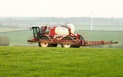 喷洒在英国领域的拖拉机庄稼 免版税库存照片