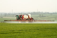 喷洒在英国领域的拖拉机庄稼 库存照片