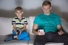 使用电话的孩子看电视的和爸爸 免版税库存照片