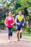 跑步或跑在健身的公园的亚洲夫妇 免版税库存照片