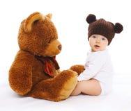 被编织的棕色帽子的逗人喜爱的婴孩有大玩具熊的 库存照片
