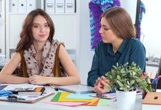 在书桌的两位时装设计师 免版税库存图片