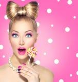 吃棒棒糖的滑稽的女孩 免版税库存照片