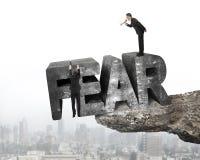 使用扩音机雇员垂悬的恐惧词边缘峭壁城市的上司 免版税图库摄影