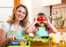 母亲和孩子烹调和获得乐趣在厨房里 免版税库存照片
