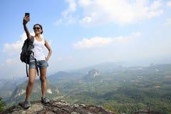 拍与手机的妇女远足者照片 库存图片