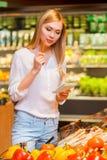 Выбирать вверх продукты от ее списка Стоковые Изображения RF