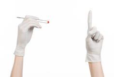 药理和医疗题材:在拿着有红色药片胶囊的一副白色手套的医生的手镊子隔绝在白色背景 图库摄影