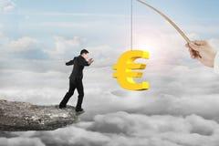 Человек балансируя золотой прикорм рыбной ловли символа евро с солнцем заволакивает Стоковое Изображение