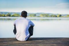 一个湖的英俊的年轻人晴朗的,平安 库存照片