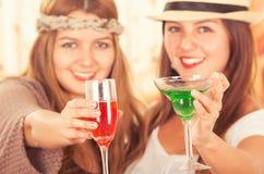 拿着他们的鸡尾酒的两个乐趣美丽的女孩 免版税库存图片