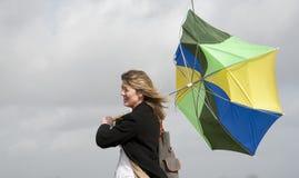 努力的妇女拿着她的伞在一个大风天 免版税库存照片