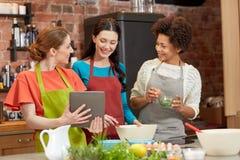 有片剂个人计算机的愉快的妇女烹调在厨房里的 免版税库存图片