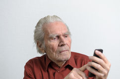 Пожилой человек пишет отправку СМС используя его мобильный телефон Стоковые Изображения