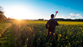 看油菜籽花田的农夫 免版税库存图片